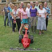 St Denis' church East Hatley, Cambridgeshire – some of the team Hatley volunteers who tidy up the churchyard three or four times a year with the 'St Denis mower'. L-to-r Kevin Steel, Sarah Brennan, Angela Steel, Carole Cooper, Sue Wright, John Wright, Nicola Jenkins, Joyce Denby, Mervyn Lack, Becky White, John Lanchbery, Jo Hayward, Peter Hayward and hiding behind the camera, Peter Mann – 16-7-17.