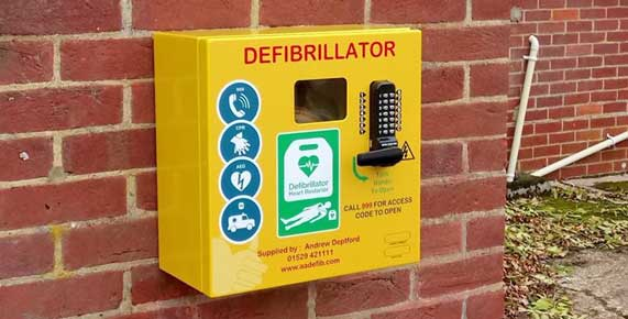 The defibrillator cabinet outside Hatley Village Hall. If you need to use it, first dial 999 – it has been registered with the NHS who will provide the code to open the cabinet door and give instructions for its use.